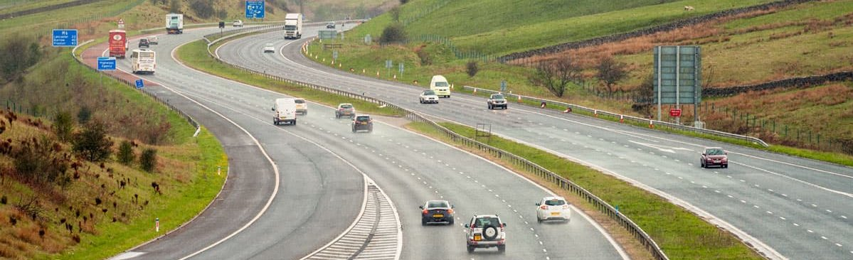 Cars, buses and HGV in the rain on the M6 in England.